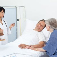 Man in hospital bed looking at wife with doctor