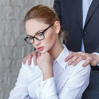 Man giving woman shoulder rub in the workplace